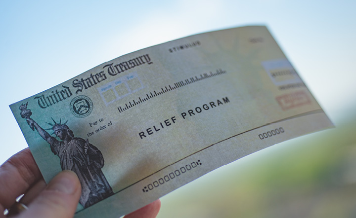 "A hand holding a check labeled ""relief program"" from the United States government"